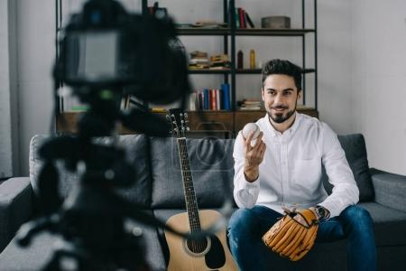 sport blogger recording new video about baseball and holding ball and mitt