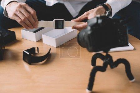 Photo pour Cropped image du blogueur technologie tenant nouvelle smart montre devant la caméra - image libre de droit