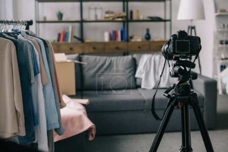 different clothes on hangers on stand in empty room