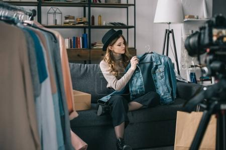 young fashion blogger sitting in front of camera with jean jacket