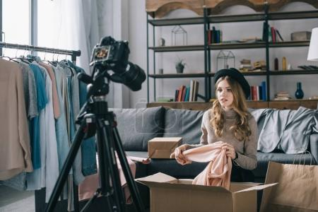 Photo for Young fashion vlogger sitting in front of camera with shirt - Royalty Free Image