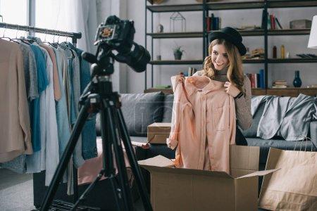 smiling fashion blogger recording new vlog about shirt