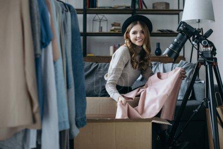 smiling fashion blogger holding dress and looking at camera
