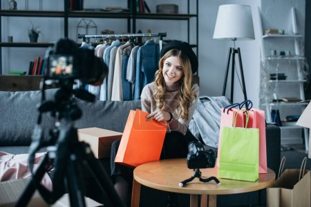 Photo for Smiling fashion blogger sitting with shopping bags and recording new video for vlog - Royalty Free Image