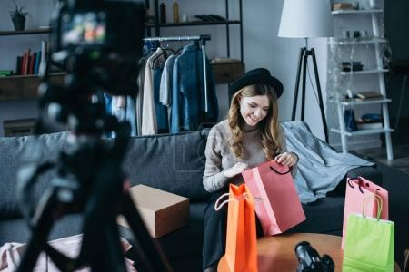 smiling fashion blogger looking into shopping bags and recording new video for vlog