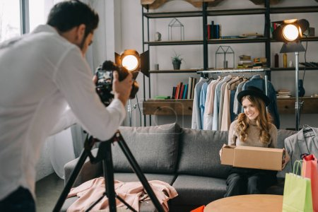 man shooting female fashion blogger with new clothes in box