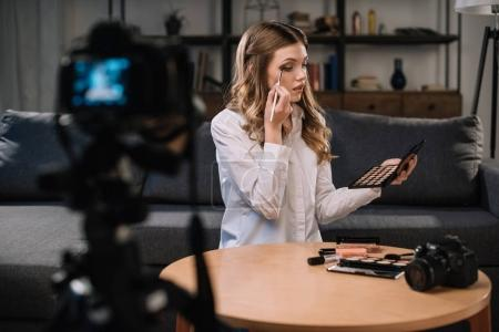 beauty blogger applying eyeshadow in front of camera