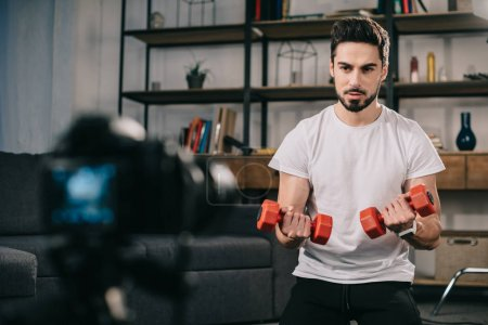 sport blogger showing how to train with dumbbells