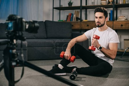 sport blogger sitting on floor and showing how to train with dumbbells