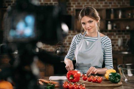 Photo pour Nourriture jeune blogueur coupe tomates cerises - image libre de droit