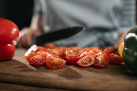 Photo for Cropped image of cook cutting cherry tomatoes on wooden board - Royalty Free Image