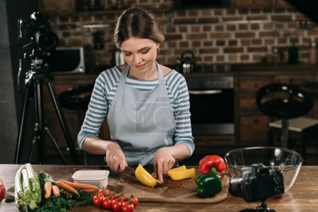 young food blogger cutting bulgarian peppers