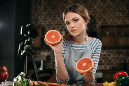 Foto de Blogger de alimentos joven mostrando mitades de pomelo a la cámara - Imagen libre de derechos