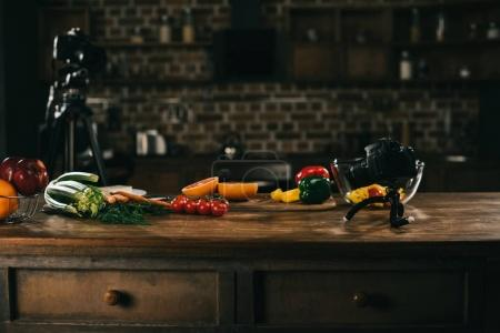 wooden table with vegetables, fruits and cameras