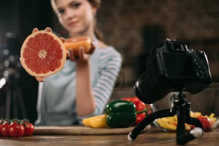 young food blogger showing half of grapefruit to camera