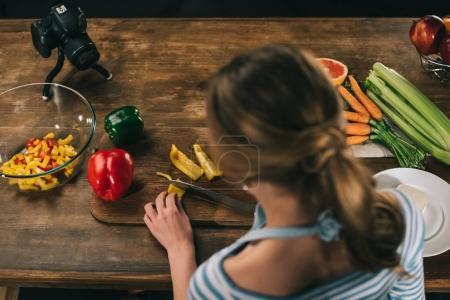 Foto de Vista aérea de alimentos mujer blogger cortar pimientos - Imagen libre de derechos