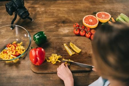 Photo pour Vue aérienne de nourriture blogger cutting poivrons - image libre de droit