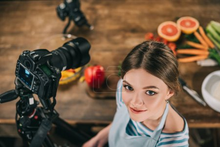overhead view of attractive food blogger looking at camera