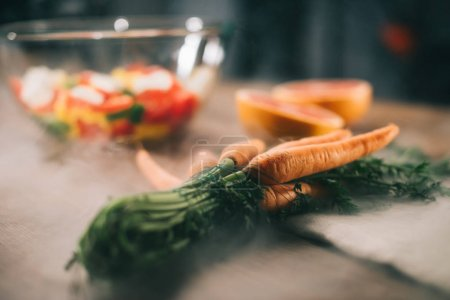 ripe carrots on wooden table with vegetables on blurred background