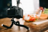 digital camera on table with salad on blurred background