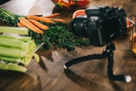 Photo pour Appareil photo numérique et les légumes sur la table en bois - image libre de droit