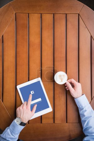 Photo for Cropped image of man sitting with coffee and loaded facebook page on tablet - Royalty Free Image