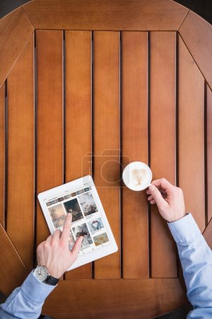 cropped image of man sitting with coffee and loaded pinterest page on tablet