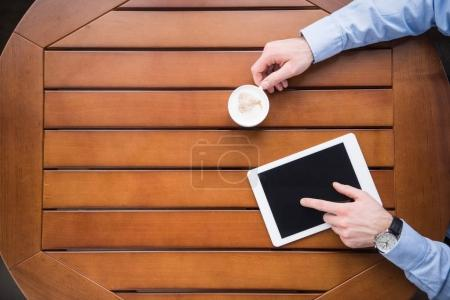 cropped image of man using tablet and holding cup of coffee