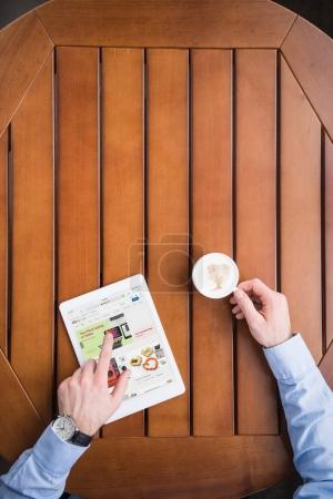 cropped image of man sitting with coffee and loaded ebay page on tablet