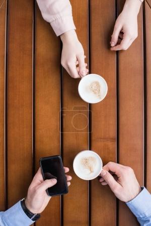 cropped image of man and woman sitting with cups of coffee and man using smartphone