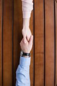 cropped image of boyfriend and girlfriend holding hands at table
