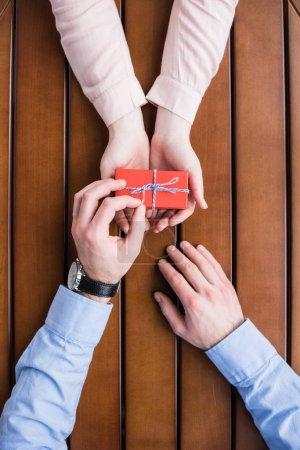 cropped image of boyfriend untying ribbon bow on present box