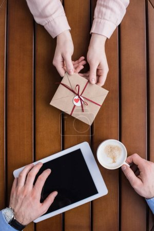 cropped image of girlfriend gifting postcard in envelope to boyfriend with tablet and coffee