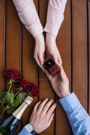 cropped image of boyfriend proposing girlfriend and holding wedding ring