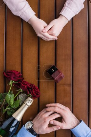 cropped image of couple sitting at table with wedding ring between them