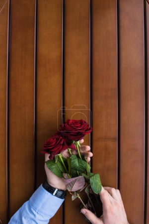 cropped image of man holding bouquet of red roses at table