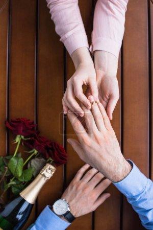 Cropped image de petite amie portait la bague sur le doigt de copain