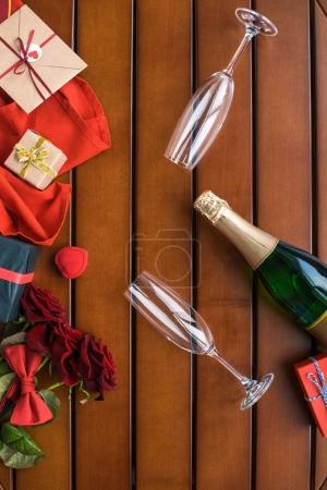 top view of glasses and bottle of champagne with presents on table