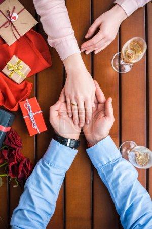 Photo pour Image recadrée de copain tenant copines main avec anneau de mariage - image libre de droit