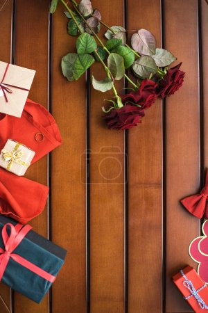 top view of bouquet of red roses and presents on table