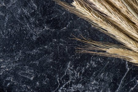 close up view of wheat on dark marble tabletop