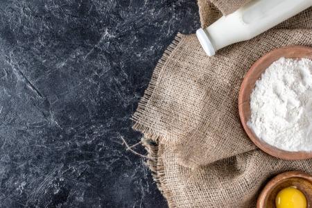 Photo pour Vue du dessus de la bouteille de lait, jaune et farine sur un sac sur une table en marbre foncé - image libre de droit