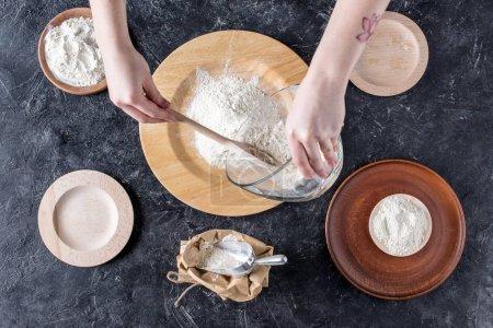Photo pour Plan recadré de femme mélangeant des ingrédients pendant la cuisson du pain - image libre de droit