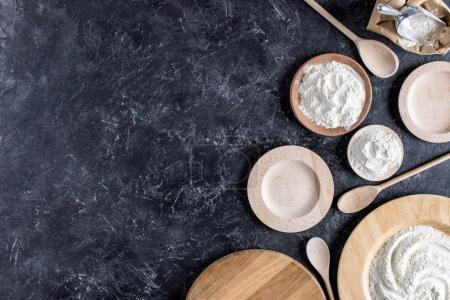 flat lay with arrangement of wooden plates, spoons and flour on dark marble tabletop