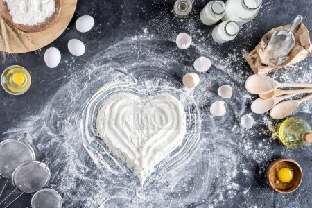 top view of heart sign made of flour and various ingredients for baking on dark surface