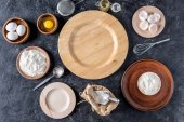 flat lay with wooden plates and bakery ingredients on dark surface