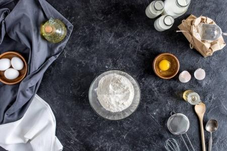 top view of arranged kitchenware and ingredients for bread baking on dark marble surface