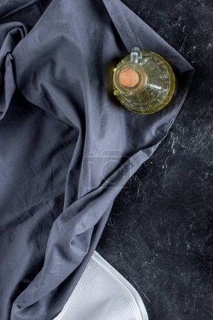 top view of bottle of oil and tablecloth on dark marble tabletop
