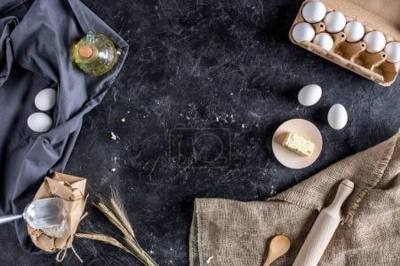 flache Lage mit verschiedenen Zutaten zum Brotbacken und Besteck auf dunkler Marmoroberfläche