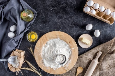 flat lay with various ingredients for bread baking and cutlery on dark marble surface